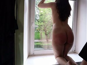 She is belt spanked in front of the window